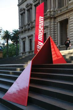 "The team designed bright red ""folded"" monumental signs that are ""contemporary insertions"" into the historic setting (an approach not appreciated by some more conservative members of the public, according to emerystudio). The 25mm and 40mm steel plate sign sculptures are located to subtly guide visitors upward to discover the museum entry and exhibitions."