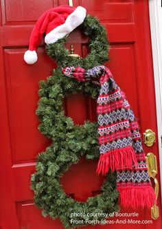 Make a cute snowman wreath for your front door with just 3 greenery wreaths, a scarf and a hat.  More wreath ideas on Front Porch Ideas and More.