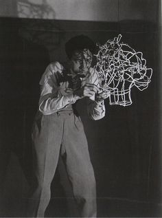 Jean Cocteau, sculpting his own head in wire,c.1925. Photograph by Man Ray.
