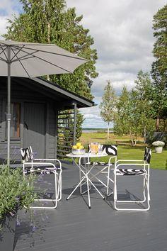 Aittojen eteen rakennettiin leveä terassi. Ohjaajantuolit terassipöydän ympärillä päällystettiin Marimekon mustavalkealla kankaalla.