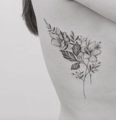 Delicate black and grey ink floral tattoo on rib cage by Tritoan Ly: