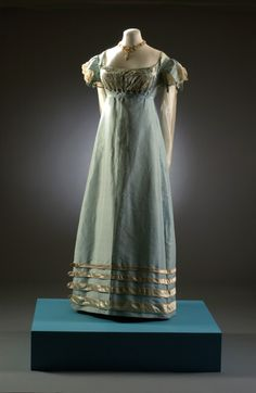 Long duck egg blue dress with cream detail. Number: BATMC I.09.1258  Material(s): silk. Technique(s): woven (taffeta), woven (net) and woven (satin)  Creation date: 1817-1821. Fashion Museum, UK.