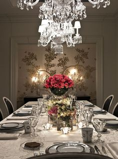Elegant dining room table always leaves room for romance... the tiered rose vases and crystal lighting make the table pop out from the gorgeous candelabras and gilded vintage style Orient floral wallpaper.