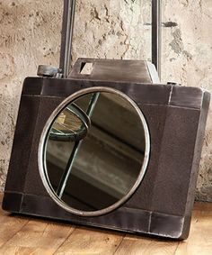 Decorate the wall with this one-of-a-kind mirror, fashioned after an antique camera. The durable metal construction makes this piece a sturdy, eye-catching addition to any space.