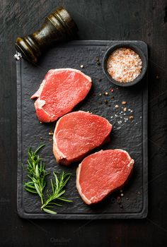 #Raw beef Eye Round steaks  Raw beef Eye Round steaks with spices and rosemary on black slate stone board over dark wooden background top view vertical composition