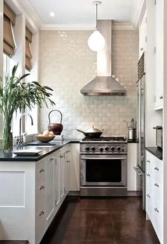 Narrow black and white kitchen with hardwood floors, silver accents and bright white subway tiles.