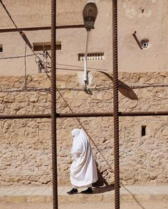 Luís Octávio Costa (@kitato) photographs a woman in the streets of #Ghardaia #Algeria writing The Mozabite women are draped in long thick white veils which allow only one eye to be seen. Photographing these women from the front he says is strictly forbidden. Costa continues Installed in Ghardaia for centuries the #Mozabite community operates in closed circuit with its codes and rules. More from Algeria at @kitato. This image was submitted using the hashtag #myfeatureshoot…