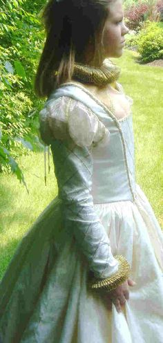 This side view of a girl's dress shows the elegance the woman possessed.  They wore a long, white garment resembling a nightdress (a chemise), stockings, a leather corset, waist-petticoats, a bodice, and a gown over it. Girls and women would always cover their hair, usually with a scarf or a hat.