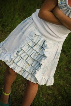 To make this style, you are going to make two layers of skirts.  The wrap-around, outerskirt is one long rectangle with a curved corner at the base of each side and a ruffle attached all the way around the edge.  The underskirt has stacked, horizontal ruffles that peek out when the outerskirt separates at the center front.