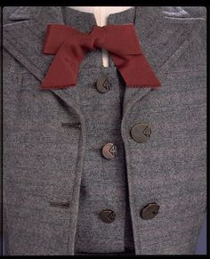 Grey herringbone wool skirt suit fastened with metal buttons, trimmed with a grosgrain bow. Made in London, England- Autumn 1942 (designed) Artist/Maker: Digby Morton Incorporated Society of London Fashion Designers- Utility (follow link to V website for more information)
