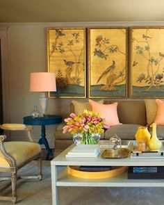 Pastel peach, canary yellow, and gold accessories appear to glow against the olive khaki shades of the walls, carpet, and sofa. Source