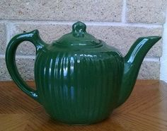 """Vintage Fraunfelter China Dark Green Teapot $10 This beautiful ribbed teapot is made by Fraunfelter China of Ohio. The Fraunfelter Company opened in 1915 and closed in 1939, so this teapot is 1930s or older. The overall ribbed shape and curved handle make these charming for serving tea or water for hot chocolate. The teapot holds 28 ounces and is approximately 9"""" long from spout to handle, 4 1/2"""" wide, and about 6"""" tall. A great addition for someone's collection, and of course to use at tea…"""