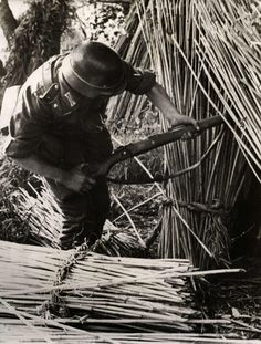 A German soldiers searches a hay stack...
