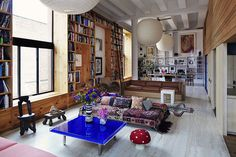 This space is amazing. Love all the bookshelves, the art, the pops of color in the furniture and accessories, the interesting architectural beams across the ceiling, the open loft feel, etc.