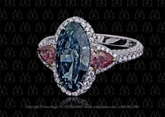 Montpassier three-stone ring featuring an oval blue diamond and two pink…