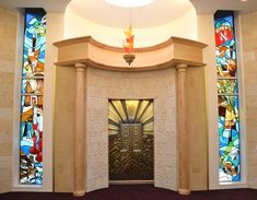 Anshe Sfard Synagogue in Akron, Ohio. The stained glass windows are located on either side of the Holy Ark in the main sanctuary. At the top of both window is an arch that defines the double tablets that symbolize the Ten Commandments. This theme is carried down through the entire artwork by the Hebrew numerals. 1-5 and 6-10 Although these two windows are separated by about 15 feet, they are tied together into one artwork by the open Torah scroll that spans both windows (done in brown…