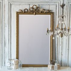 Eloquence, Inc. Antique French Mirror: 1880 This antique French mirror has a large, sweet bow motif at the center. The deep gilt finish and swirls along the frame give it a feminine feel, and the ornate carvings at the inner edge of the frame add complexity.