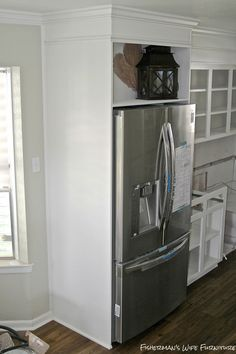 built-in fridge enclosure in a small white kitchen, Fisherman's Wife Furniture featured on Remodelaholic.com
