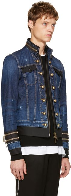 Long sleeve layered denim jacket in blue. Paneled wool and silk-blend mock blazer inner layer in black. Fading, and distressing throughout. Zip accents at stand collar and cuffs. Two-way zip closure and decorative button placket at front. Flap pockets at chest. Buttoned cuffs. Adjustable cinch straps at back waistband. Gold-tone hardware. Contrast stitching in tan.