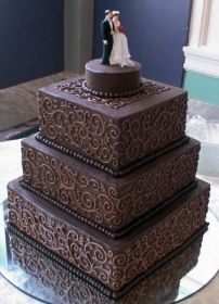 I could totally love an all chocolate wedding cake. But still maybe white or colors of the theme.   Love the detailing.