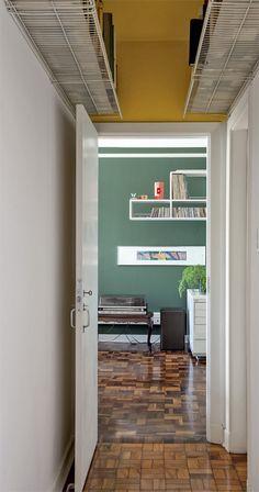 Livros do morador ocupam prateleiras aramadas fixadas na parte alta do corredor, que foi pintada de amarelo. Para que os exemplares mais finos não escorreguem, foi providenciada uma base de plástico fosco.