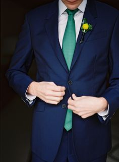 Colour blocking groom, navy suit with teal tie
