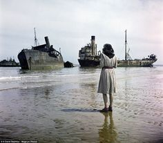 A woman stand on Omaha Beach looking out at the rusted ship used in the D-Day invasion of Normandy. During the assault, some 150,000 Allied troops stormed the French beach in order to grasp a foothold on Nazi-occupied France and begin their liberation of Europe
