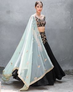 This set features a black blouse in satin cotton base embroidered with gold zari and sequins leaf work all over the front, back and sleeves. It is paired with matching lehenga with embroidery on the waist and mint green net dupatta. Ethnic Outfits, Indian Outfits, Indian Attire, Indian Wear, Indian Style, Black Lehenga, Silk Lehenga, Indian Designer Suits, Desi Wear
