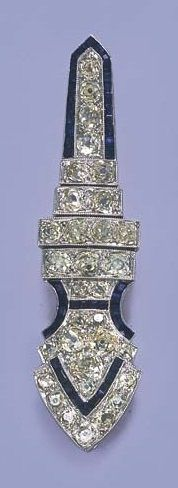 A belle époque diamond and sapphire brooch by Chaumet. Of arrow design, set with light yellow old-cut diamonds to the calibré-cut sapphire detail, circa 1915, 6.2 cm. long, with French assay mark for platinum and gold. Signed JC for Jacques Chaumet.