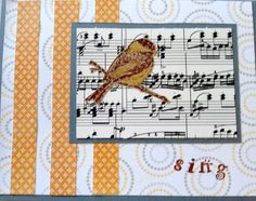 """Used a blue-gray card for this one; found some background paper that sort of matched. Added 3 strips of another color in the background and a square of music backed with the card color. The bird was stamped in black on brown paper and cut out. Added the """"sing"""" with my mini alphabet stamps..."""