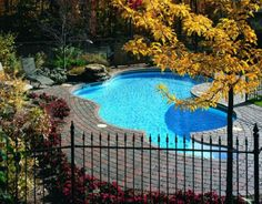 Swimming Pool: Appealing Stone Pool Deck Design Private Outdoor Swimming Pool With Red Grey Paving Stone Also Metal Fence And Grey Pool Chairs Design Ideas: Mesmerizing Stone Pool Deck Design Ideas