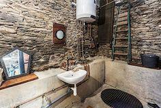 Letmý pohled do koupelny odhalí mohutnou podezdívku a originální vodovodní baterii z topenářských fitinek.