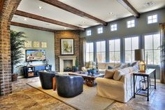 A closer view of the living room shows the angled wall covered in adobe bricks. The veneer easily blends into, yet provides a stark contrast in color and texture to the gray-green paint and white fireplace mantle. The stone floors are covered by a large beige area rug.