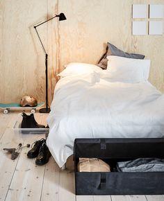 Dve rôzne úložné škatule pod posteľ vedľa postele.