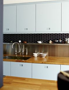 Ice blue kitchen cabinets with routed out handles, solid oak countertop, stainless steel backsplash and shelf, black hexagonal tiles | Remodelista