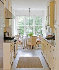 Cheerful yellows and a well-lit breakfast space open up this galley kitchen - Traditional Home® / Photo: Erik Johnson / Design: Loi Thai