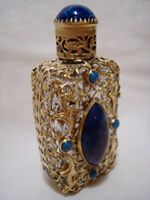VINTAGE CZECH FILIGREE PERFUME BOTTLE JEWELED SIGNED.THIS LITTLE BEAUTY IS ALMOST 2 1/2 IN. TALL. SHE IS NICELY WRAPPED IN A DETAILED FILIGREE WITH 4 LITTLE TURQUOISE STONES THAT SURROUND A BIG ROYAL BLUE & TURQUOISE MARBLED STONE THAT IS PEPPERED WITH GOLD FLAKES. HER FILIGREE CAP FEATURES A BEAUTIFUL ROYAL BLUE & TURQUOISE STONE ON TOP(NO GOLD FLAKE). CAP IS SIGNED CZECH.  $245.00