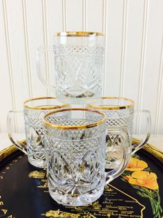 This is a set of four crystal cut glass with gold rim drinking mugs. Beautiful like new condition, these mugs would be wonderful for your next cocktail party, displayed on bar cart, in hutch or kitchen tray on island! Would make a lovely wedding or shower gift! USA stamped on bottom. Will ship insured!  Measures each almost 4H X 3 diameter 4W with handle  Thanks for shopping YellowHouseDecor!  Please visit my sisters shop for more vintage items ( ellansrelics02)   Tray sold separately
