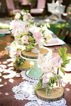 Pink and mint wedding reception decor at an outdoor table with cake stand and wood cut centerpiece platforms.