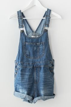 Slightly distressed short denim overalls with rolled up bottom hem. Large front…