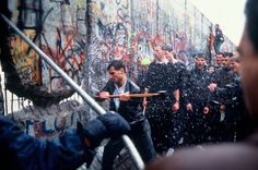 Fall of the Berlin Wall -- Men hammering through the Wall as East German guards fire water cannon through the crack, soaking everyone on that freezing morning. - Alexandra Avakian