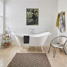 A monochrome rug adds pattern and texture to the reclaimed floorboards in this modern bathroom