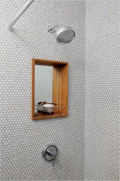 rental redo: They finished the walls and floor with penny tiles and installed a mirrored teak niche in the shower.