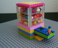 This candy dispenser provides a fun way to get a delicious sweet treat. A simple slider mechanism doles out the goods and the top has an easy-release lid. The Lego Candy Dispenser is a super simple build and doesn't take a bunch of crazy pieces but still results in an impressive way to share your candy with friends. The dispenser is made of four main parts: -base -reservoir -lid -slider The steps are labeled accordingly.