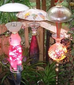 Made from old glassware.how clever,and they have lights in them.bet they are pretty at night! Use in Moonlight Garden by Pergola Garden Whimsy, Garden Junk, Diy Garden, Garden Crafts, Garden Projects, Night Garden, Garden Paths, Garden Totems, Glass Garden Art