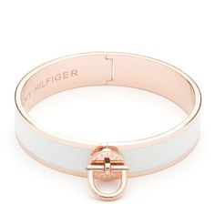 Hot trend this season: rose gold. Stand out with this rose gold-toned bangle with white enamel inset. Eye-catching twist lock with Tommy Hilfiger logo embossed at the front, delicate hinge at the back for easy on and off. Logo lettering inside the bangle.