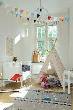 decoração quarto de bebê com bandeirinhas em tecido coloridos penduradas no teto. cabaninha para bebê brincar com almofadas