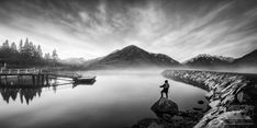 Anthony utilises the compositional elements such as the curvature of the quay at Lake Brunner, the reflections, and the fanning clouds to frame the rising mountain in the background. The solitary fisherman in the foreground invites the viewer to project themselves into the scene and get lost in this mysterious landscape. Landscape Photos, Landscape Photography, Black And White Landscape, Nature Images, West Coast, Mysterious, New Zealand, Invites, Mountain