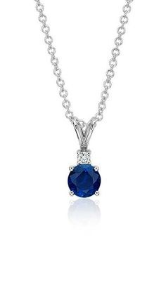 Elegant and delicate, this pendant features a round sapphire complemented by a petite diamond and is set in 18k white gold.