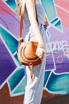 Dash of Darling styles a stripe jumpsuit paired with a leather braided Chloe marcie cross body bag